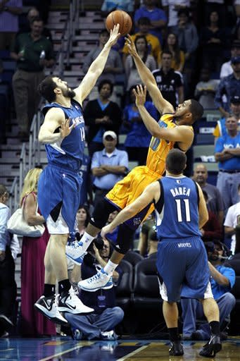 New Orleans Hornets shooting guard Eric Gordon (10) shoots over Minnesota Timberwolves center Nikola Pekovic (14) in the first half of an NBA basketball game in New Orleans, Saturday, April 7, 2012. (AP Photo/Gerald Herbert)