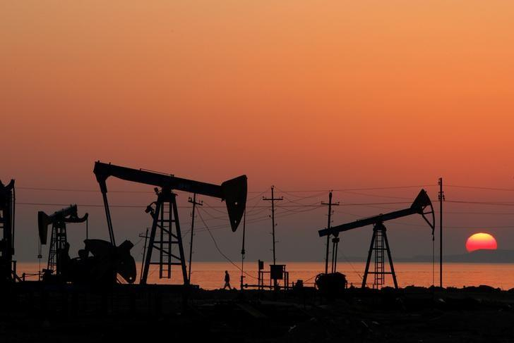 FILE PHOTO: Pump jacks are silhouetted against the rising sun on an oilfield in Baku