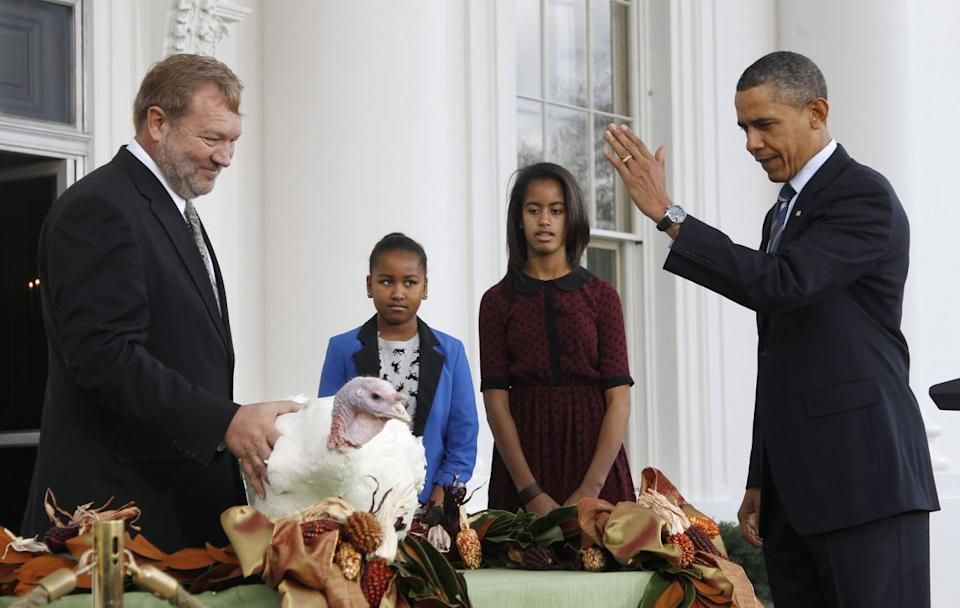 """President Barack Obama, with daughters Sasha and Malia, pardons """"Liberty,"""" a 19-week old, 45-pound turkey, on the occasion of Thanksgiving, Wednesday, Nov. 23, 2011, on the North Portico of the White House in Washington. At left is National Turkey Federation Chairman Richard Huisinga. (Photo: Pablo Martinez Monsivais/AP)"""