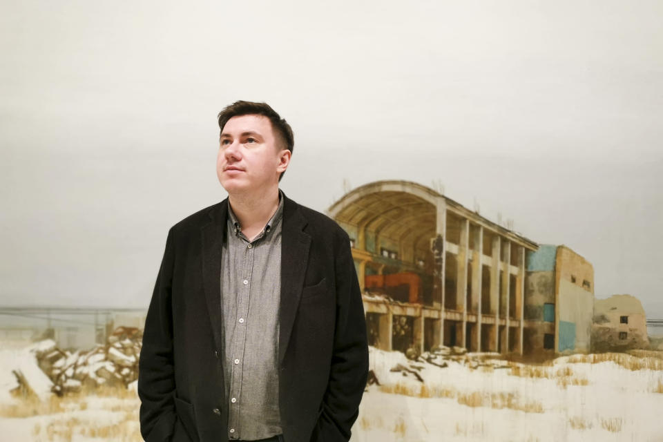 "In this photo taken on Sunday, Feb. 17, 2019, Pavel Otdelnov, a Russian artist poses for a photo in front of his work ""Ruins #4"" at his an exhibition in Moscow, Russia . Pavel Otdelnov, a Russian artist who grew up in Dzerzhinsk, the center of the nation's chemical industries 355 kilometers (220 miles) east of Moscow, focused on the city, one of the most polluted in Russia, in his new 'Promzona' art show. (AP Photo/Ivan Kochkarev)"