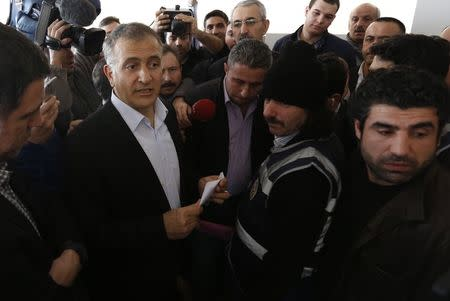 Zaman editor-in-chief Dumanli talks at his office as he is surrounded by his colleagues and plainclothes police officers at the headquarters of Zaman daily newspaper in Istanbul