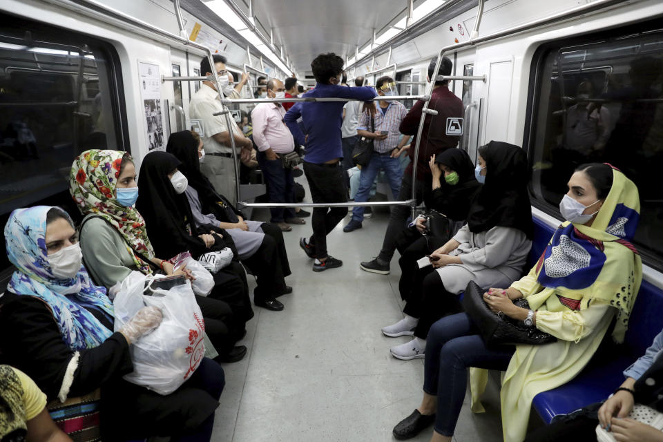 People wearing protective face masks to help prevent the spread of the coronavirus sit inside a train in Tehran, Iran, Wednesday, July 8, 2020. (AP Photo/Ebrahim Noroozi)