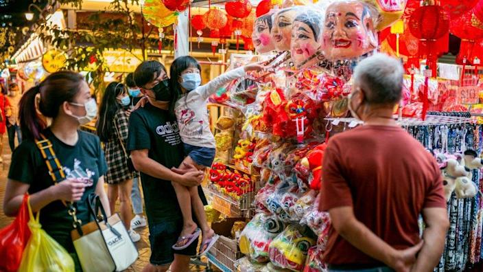 People wearing facemasks as a precaution against the spread of covid-19 browse for Chinese New Year decorations in Chinatown during the eve of the Lunar New Year.