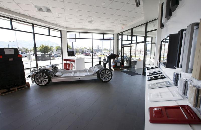 An employee sets up a display at an showroom at a new Tesla dealership in Salt Lake City