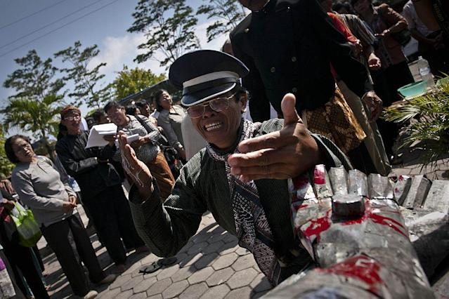 An Indonesian Catholic praying by a statue of Jesus Christ made of zinc plate during the procession of a re-enactment of the crucifixion of Jesus Christ on Good Friday 2012 in Klaten, Central Java, Indonesia. Good Friday is a public holiday in Indonesia, a majority Muslim nation.