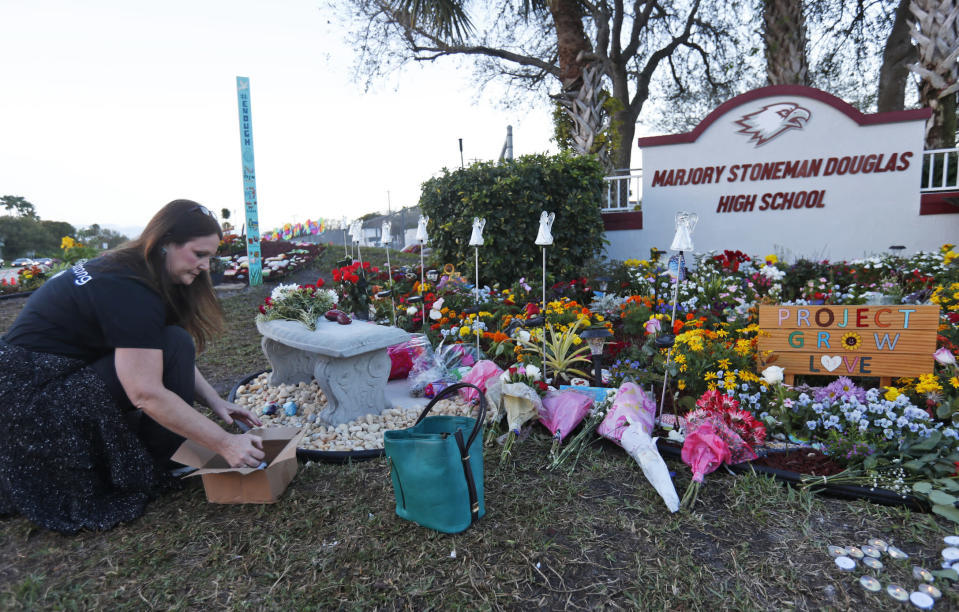 FILE - In this Feb. 14, 2019, file photo, Suzanne Devine Clark, an art teacher at Deerfield Beach Elementary School, places painted stones at a memorial outside Marjory Stoneman Douglas High School during the firstr anniversary of the school shooting in Parkland, Fla. It's been more than 1,000 days since a gunman with an AR-15 rifle burst into a Florida high school, killing 17 people and wounding 17 others. And yet, with Valentine's Day on Sunday, Feb. 14, 2021, marking the three-year milestone, Nikolas Cruz's death penalty trial is in limbo. (AP Photo/Wilfredo Lee, File)