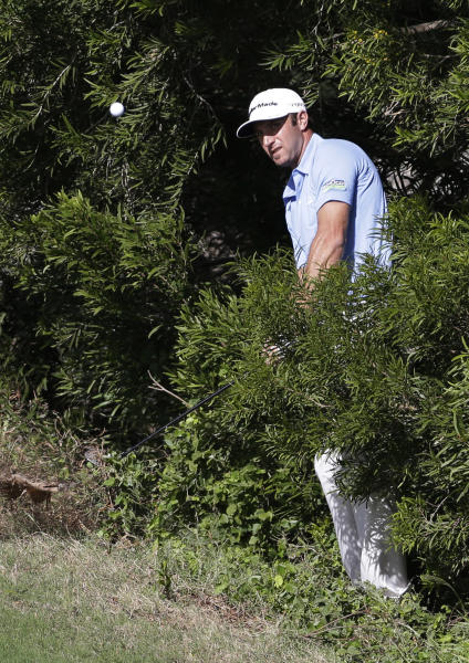 Dustin Johnson hits out of the woods on the 13th hole during the final round at the Tournament of Champions PGA golf tournament Tuesday, Jan. 8, 2013, in Kapalua, Hawaii. (AP Photo/Elaine Thompson)