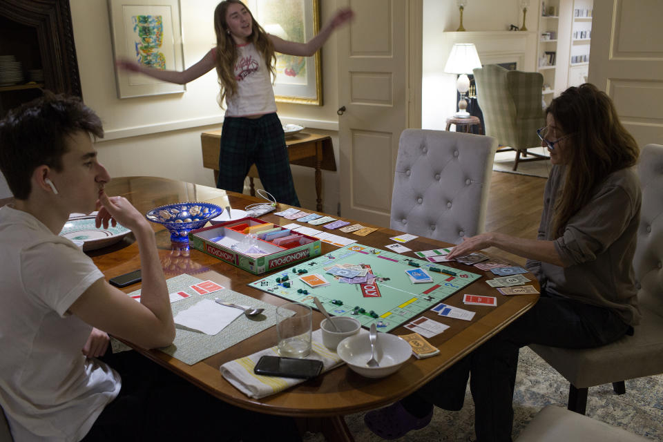 POUND RIDGE, NEW YORK - MARCH 22: A family, unable to venture beyond their home  because of the COVID-19 pandemic, play a game of monopoly together on March 22, 2020 in Pound Ridge, New York. (Photo by Andrew Lichtenstein/Corbis via Getty Images)