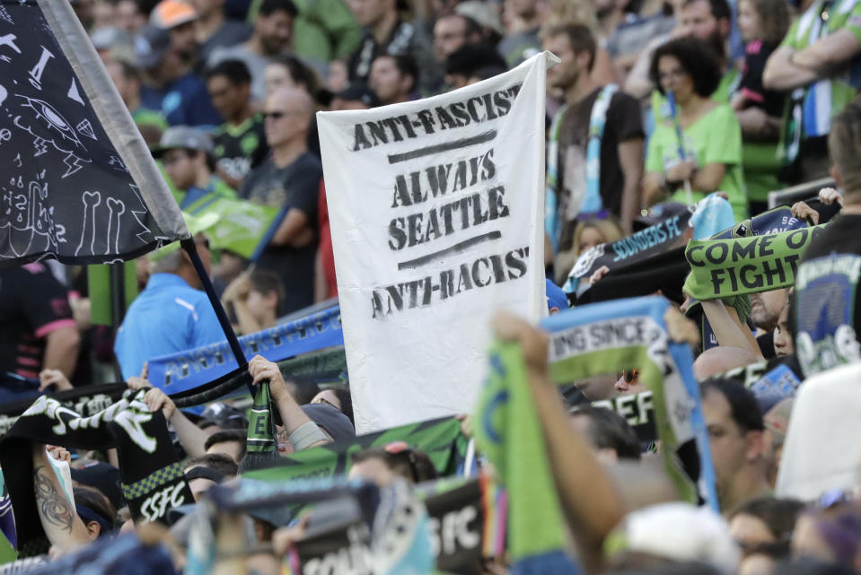 """In this July 21, 2019, photo, a sign that reads """"Anti-Facist Always Seattle Anti-Racist"""" is displayed in the supporters section during an MLS soccer match between the Seattle Sounders and the Portland Timbers in Seattle. Major League Soccer's new policy that bans political displays at matches is drawing attention in the Pacific Northwest, where supporters' culture is often intertwined with politics and social issues. (AP Photo/Ted S. Warren)"""