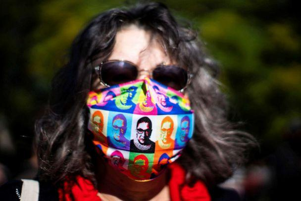 PHOTO: A woman wears a face mask with images of late Justice Ruth Bader Ginsburg as people take part in the 2020 Women's March at Washington Square park in New York City, Oct. 17, 2020. (Eduardo Munoz/Reuters)