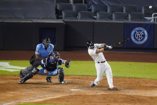 New York Yankees' Gleyber Torres hits a home run during the fourth inning of a baseball game as Toronto Blue Jays catcher Danny Jansen watches Thursday, Sept. 17, 2020, in New York. (AP Photo/Frank Franklin II)