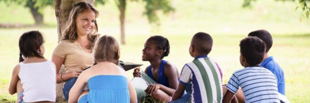 Camp counselor sitting under tree with campers.