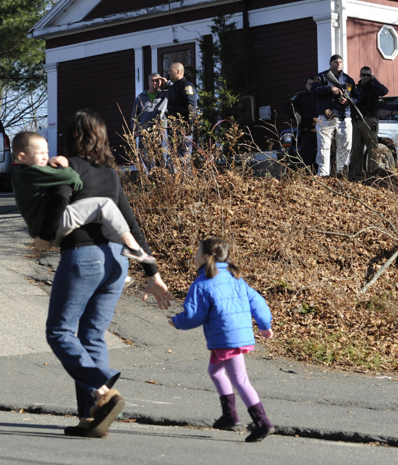 A mother runs with her children as police above canvass homes in the area following a shooting at the Sandy Hook Elementary School in Newtown, Conn., about 60 miles (96 kilometers) northeast of New York City, Friday, Dec. 14, 2012. An official with knowledge of Friday's shooting said 27 people were dead, including 18 children. (AP Photo/Jessica Hill)