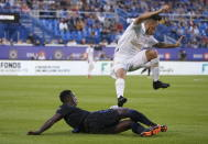 Atlanta United defender Ronald Hernandez leaps over CF Montreal midfielder Djordje Mihailovic during the first half of an MLS soccer match Wednesday, Aug. 4, 2021, in Montreal. (Paul Chiasson/The Canadian Press via AP)