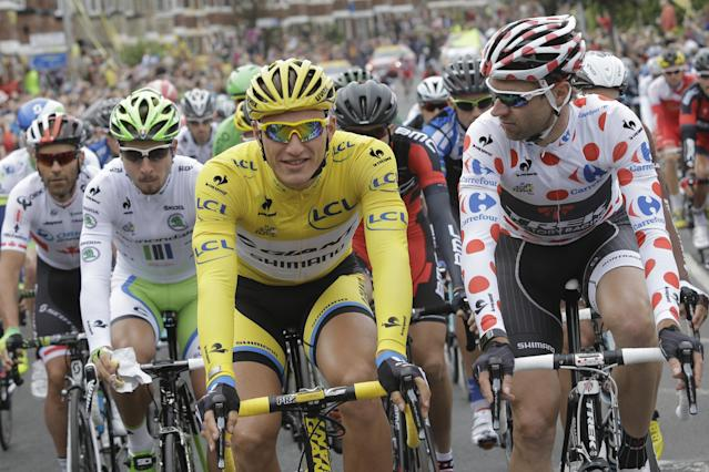 Sprinter Marcel Kittel, wearing the overall leader's yellow jersey, and Jens Voigt of Germany, wearing the best climber's dotted jersey, and Peter Sagan of Slovakia, wearing the best young rider's white jersey, second left, lead the pack during the ceremonial procession at the start of the second stage of the Tour de France cycling race over 201 kilometers (124.9 miles) with start in York and finish in Sheffield, England, Sunday, July 6, 2014. (AP Photo/Laurent Cipriani)