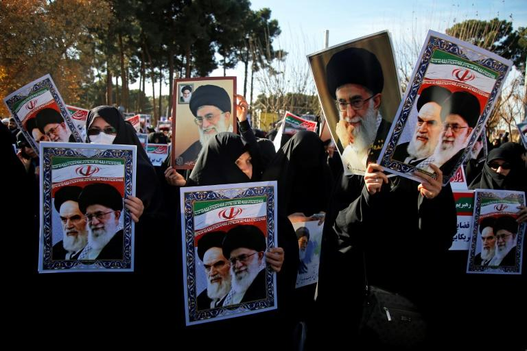 Pro-government demonstrators hold posters of Iran's supreme leader, Ayatollah Ali Khamenei (L), and the late founder of the Islamic Republic, Ayatollah Ruhollah Khomeini, in Iran's holy city of Qom on January 3, 2018
