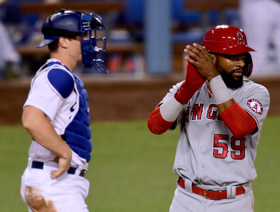 Jo Adell #59 of the Los Angeles Angels celebrates his run in front of Will Smith #16 of the Los Angeles Dodgers.