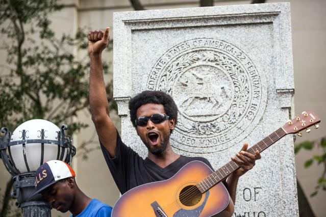 <p>Isaiah Wallace plays his guitar standing on the base that formerly supported a Confederate soldier statue after a group of protesters pulled it down during a rally Monday, Aug. 14, 2017, in Durham, N.C. (Photo: Casey Toth/The Herald-Sun via AP) </p>