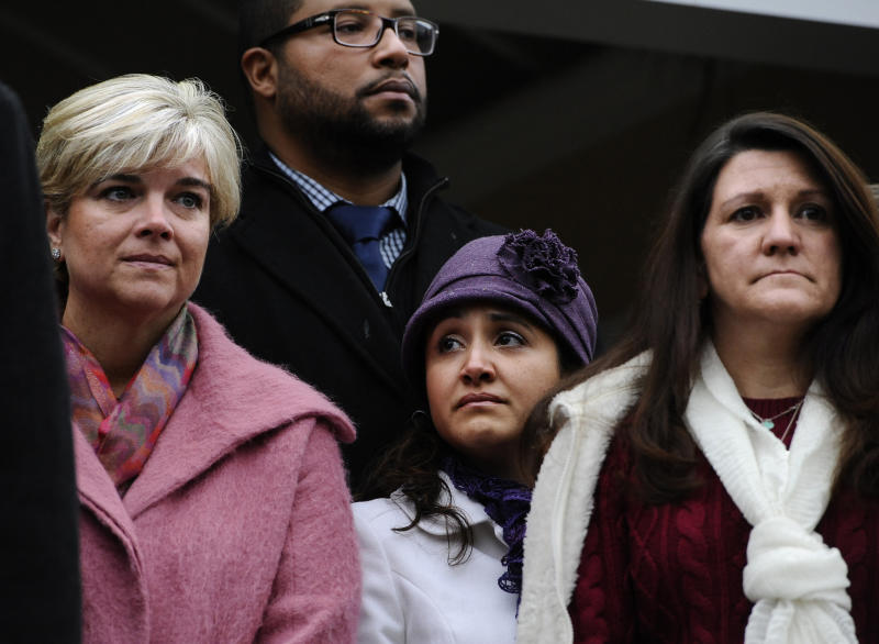 Lynn McDonnell, mother of Sandy Hook Elementary School shooting victim Grace McDonnell, left, Jimmy Greene and Nelba Marquez-Greene, center, parents of victim Ana Marquez-Greene, and Jennifer Hensel, mother of victim, Avielle Richman, right, stand with other victims' families as they address the media, Monday, Dec. 9, 2013, in Newtown, Conn. Newtown is not hosting formal events to mark the anniversary Saturday. (AP Photo/Jessica Hill)