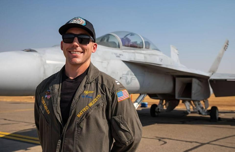 """U.S. Navy pilot Lt. Matteo """"Hog Sweat"""" Mezzetti, a Sacramento native, stands with his F/A-18F Super Hornet, also known as the """"Rhino,"""" before the California Capital Airshow on Friday, Sept. 24, 2021, at Mather Airport in Sacramento."""