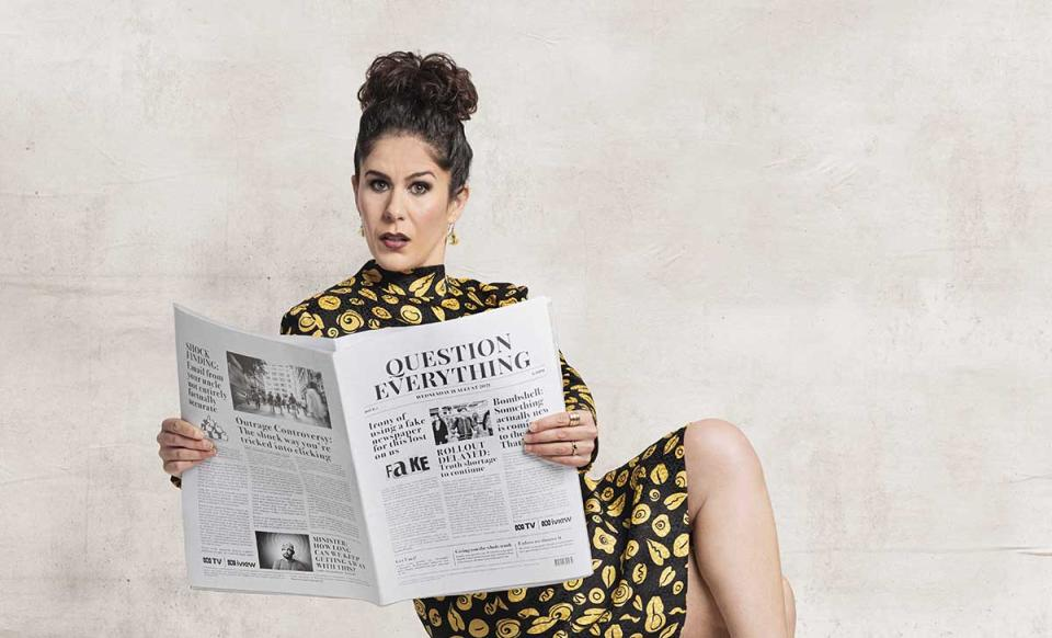 Jan Fran wearing a black and gold dress while holding a newspaper. Photo: supplied.