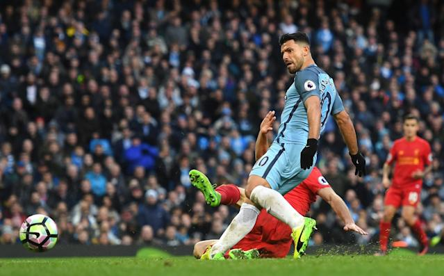 <p>Sergio Aguero slides home the ball as City level with Liverpool </p>