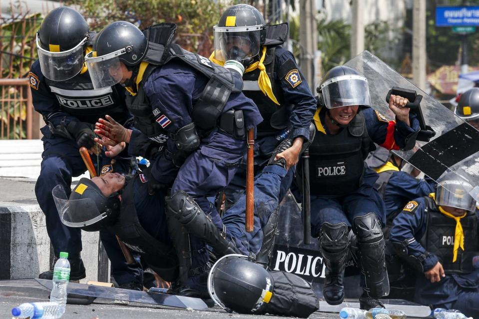 Thai riot police officers assist a colleague after an explosion during clashes with anti-government protesters near Government House in Bangkok February 18, 2014. A Thai police officer was killed and dozens of police and anti-government protesters were wounded in gun battles and clashes in Bangkok on Tuesday, officials and witnesses said. REUTERS/Athit Perawongmetha (THAILAND - Tags: CIVIL UNREST POLITICS TPX IMAGES OF THE DAY)