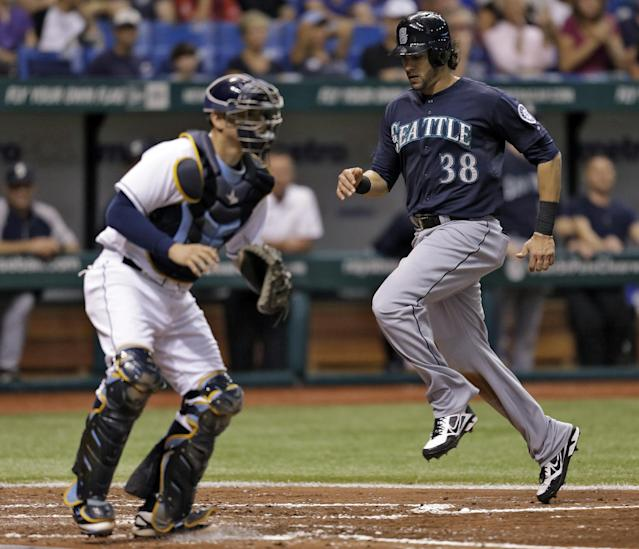 Seattle Mariners' Michael Morse, right, races home past Tampa Bay Rays catcher Jose Lobaton to score on a fourth-inning, two-run single by Justin Smoak off Rays starting pitcher Chris Archer during a baseball game Tuesday, Aug. 13, 2013, in St. Petersburg, Fla. Raul Ibanez also scored on the hit. (AP Photo/Chris O'Meara)