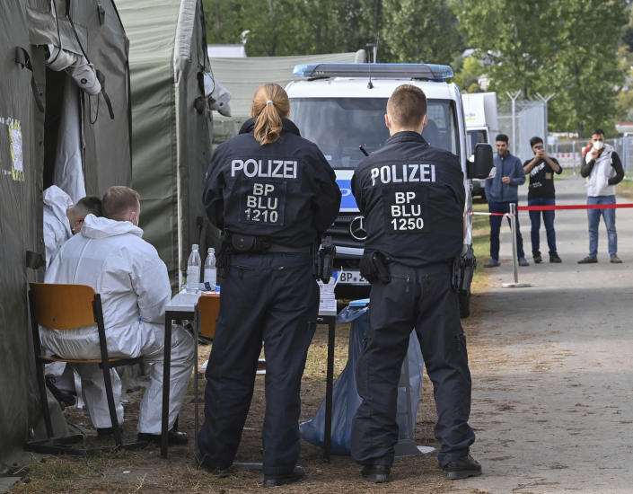 FILE-In this Oct. 6, 2021 taken photo police officers wait for migrants at the Central Initial Reception Centre for Asylum Seekers (ZABH) in the state of Brandenburg in Eisenhuettenstadt, Germany. German authorities say that the number of migrants arriving in the country via Poland and Belarus has gone up quickly during recent months. (Patrick Pleul/dpa via AP)