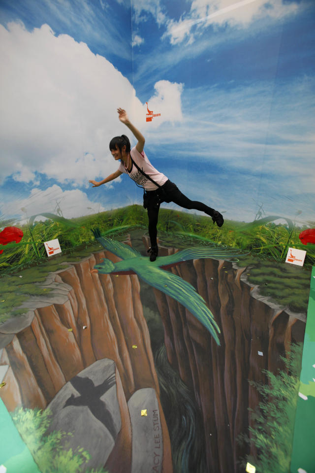 "A girl poses at a 3-D chalk drawing in an exhibition entitled ""The house of 3D Art Illusion"" at a shopping center in Hong Kong Wednesday, July 14, 2010. The interactive exhibition is open to the public to enjoy the visual experience.   (AP Photo/Kin Cheung)"