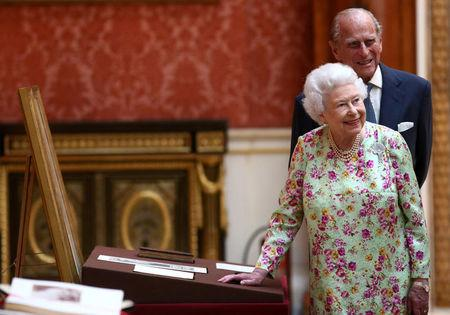 FILE PHOTO: Britain's Queen Elizabeth II and Prince Philip, Duke of Edinburgh stand next to a display of Spanish items from the Royal Collection at Buckingham Palace
