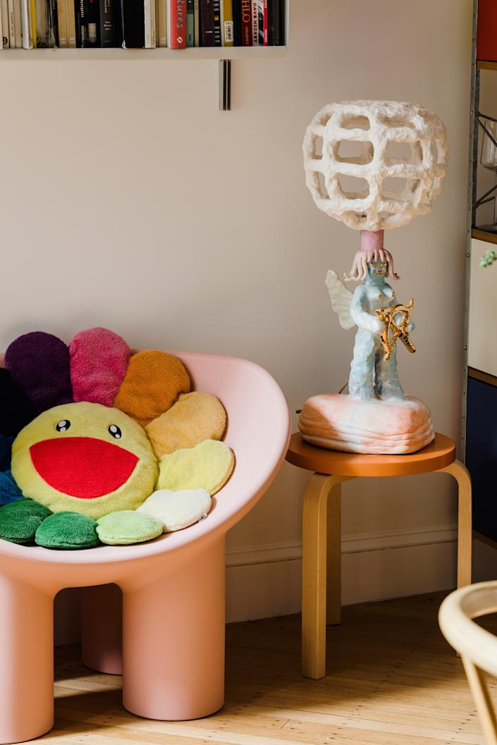 "<div class=""caption""> Another work by Katie Stout, the Angel Lamp, is displayed next to <a href=""https://www.architecturaldigest.com/story/we-all-need-childlike-design-right-now?mbid=synd_yahoo_rss"" rel=""nofollow noopener"" target=""_blank"" data-ylk=""slk:Faye Toogood"" class=""link rapid-noclick-resp"">Faye Toogood</a>'s <a href=""https://fave.co/2yzKwhn"" rel=""nofollow noopener"" target=""_blank"" data-ylk=""slk:Roly Poly chair for Driade"" class=""link rapid-noclick-resp"">Roly Poly chair for Driade</a> with a pillow by Japanese artist <a href=""https://store.moma.org/prints-artists/artist-products/murakami-flower-plush/146567-146567.html"" rel=""nofollow noopener"" target=""_blank"" data-ylk=""slk:Takashi Murakami"" class=""link rapid-noclick-resp"">Takashi Murakami</a>. </div>"