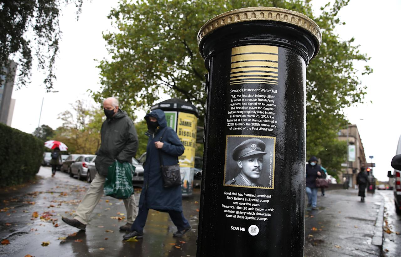 Members of the public walk past a black postbox featuring an image of Second Lieutenant Walter Tull, on Byres Road, Glasgow, one of four special edition postboxes unveiled by Royal Mail to mark Black History Month. (Photo by Andrew Milligan/PA Images via Getty Images)