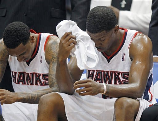 Atlanta Hawks' Joe Johnson, right, and Jeff Teague sit on the bench during a timeout late in the second half of Game 2 of an NBA first-round playoff basketball series against the Boston Celtics on Tuesday, May 1, 2012, in Atlanta. Boston won 87-80 and evened the series at one game each. (AP Photo/John Bazemore)