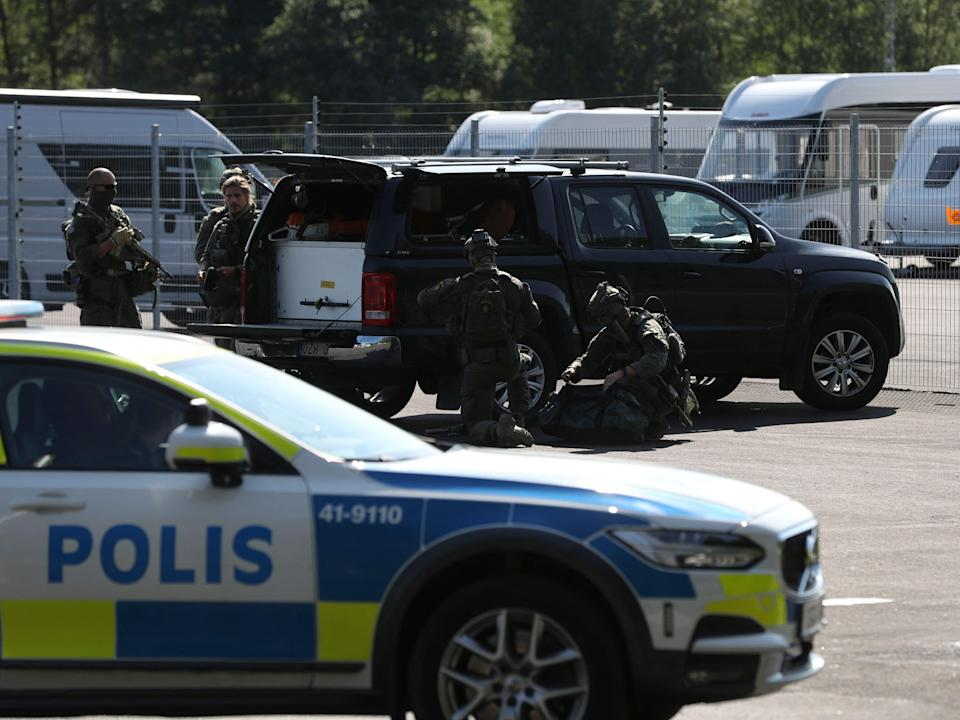 Special unit police forces are seen by a car parked outside the Hallby Prison near Eskilstuna, Sweden, July 21, 2021.