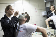 FILE - In this April 27, 2017, file photo, Yulia, wife of Russian opposition leader Alexei Navalny treats him after unknown attackers doused him with green antiseptic outside a conference venue in Moscow, Russia. The return of Navalny on Jan. 17, 2021, from Germany after he spent five months in Berlin recovering from a nerve agent poisoning was marked by chaos and popular outrage, and it ended, almost predictably with his arrest. Navalny is an anti-corruption campaigner and the Kremlin's fiercest critic. (AP Photo/Evgeny Feldman, File)