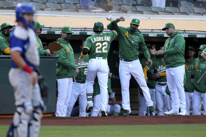 Oakland Athletics' Ramon Laureano (22) is congratulated by teammates after hitting a solo home run against the Toronto Blue Jays during the first inning of a baseball game in Oakland, Calif., Wednesday, May 5, 2021. (AP Photo/Jed Jacobsohn)