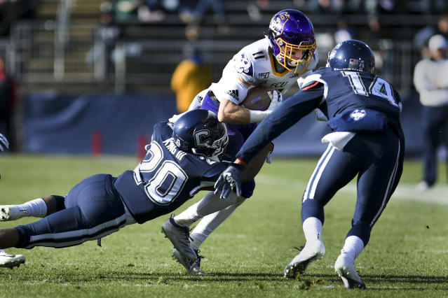 East Carolina wide receiver Blake Proehl (11) is taken down by Connecticut defensive back Robert King III (20) during the first half of an NCAA college football game, Saturday, Nov. 23, 2019, in East Hartford, Conn. (AP Photo/Stephen Dunn)