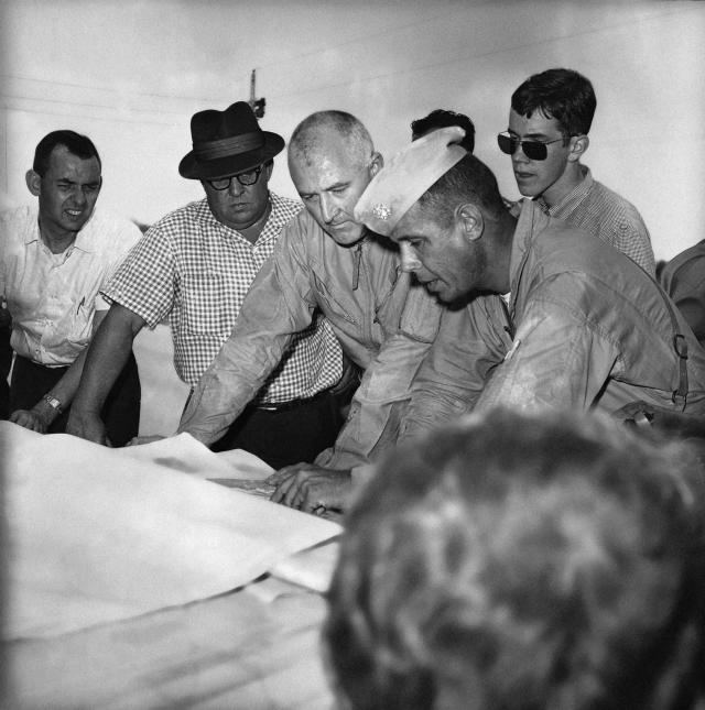 <p>Leaders of the search for three missing civil rights workers go over map of area near Philadelphia, Mississippi on June 25, 1964. They are, left to right, Gwin Cole, chief investigator in charge for Mississippi highway patrol; Joe Sullivan, FBI, Washington, and Lt. Cmdr. John Wassell, in command of the Navy people. (Photo: AP) </p>
