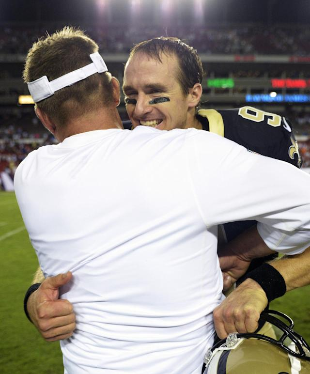 New Orleans Saints quarterback Drew Brees hugs head coach Sean Payton after the team defeated the Tampa Bay Buccaneers 16-14 during an NFL football game Sunday, Sept. 15, 2013, in Tampa, Fla. (AP Photo/Phelan M. Ebenhack)