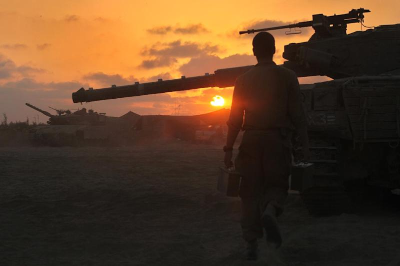 An Israeli soldier walks past a Merkava tank along the border between Israel and the Hamas-controlled Gaza Strip, on July 30, 2014