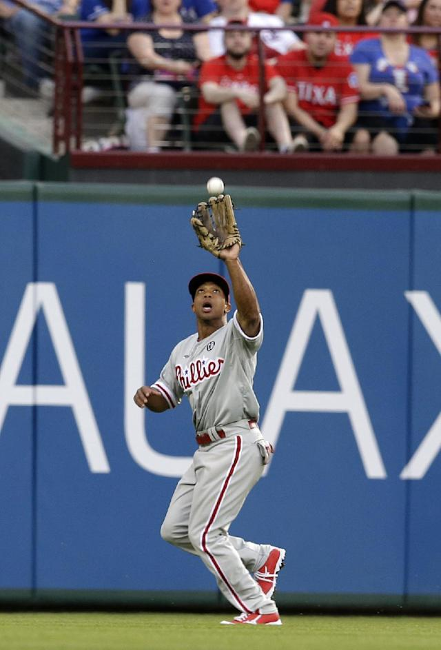 Philadelphia Phillies center fielder Ben Revere reaches up to grab a fly-out by Texas Rangers' Prince Fielder in the first inning of a baseball game, Tuesday, April 1, 2014, in Arlington, Texas. (AP Photo/Tony Gutierrez)
