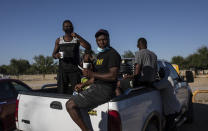 Migrants board the back of a truck at an encampment after agreeing to be transferred to a shelter, in Ciudad Acuna, Mexico, Friday, Sept. 24, 2021, across the Rio Grande from Del Rio, Texas. No migrants remained Friday at the Texas border encampment in Del Rio where almost 15,000 people — most of them Haitians — had converged just days earlier seeking asylum, local and federal officials said. (AP Photo/Felix Marquez)