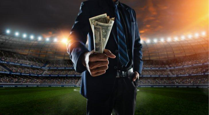 A person wearing a suit and tie holds a handful of dollar bills in the middle of a brightly lit sports stadium representing HLBZ stock.