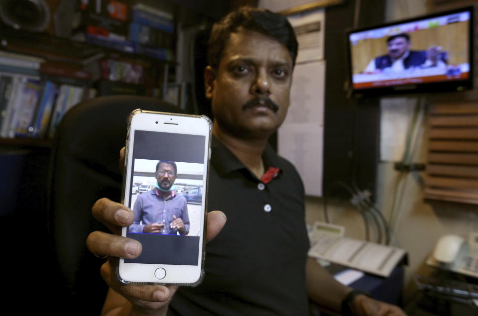 """Fahim Siddiqi, Karachi bureau chief of Geo News television, shows the picture of missing colleague Ali Imran Syed, at his office in Karachi, Pakistan, Saturday, Oct. 24, 2020. The Geo bureau chief said Saturday that police registered the journalist's disappearance as an """"abduction"""" case without naming suspects. (AP Photo/Fareed Khan)"""