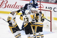 Pittsburgh Penguins' Marcus Pettersson (28), Brandon Tanev (13) and Teddy Blueger (53) celebrate with Zach Aston-Reese after Aston-Reese's goal agains Winnipeg Jets goaltender Laurent Brossoit (30) during first-period NHL hockey game action in Winnipeg, Manitoba, Sunday, Oct. 13, 2019. (Fred Greenslade/The Canadian Press via AP)
