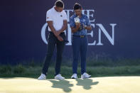 United States' Collin Morikawa, right, holds the claret jug trophy with the leading amateur Germany's Matthias Schmid on 18th green after winning the British Open Golf Championship at Royal St George's golf course Sandwich, England, Sunday, July 18, 2021. (AP Photo/Peter Morrison)