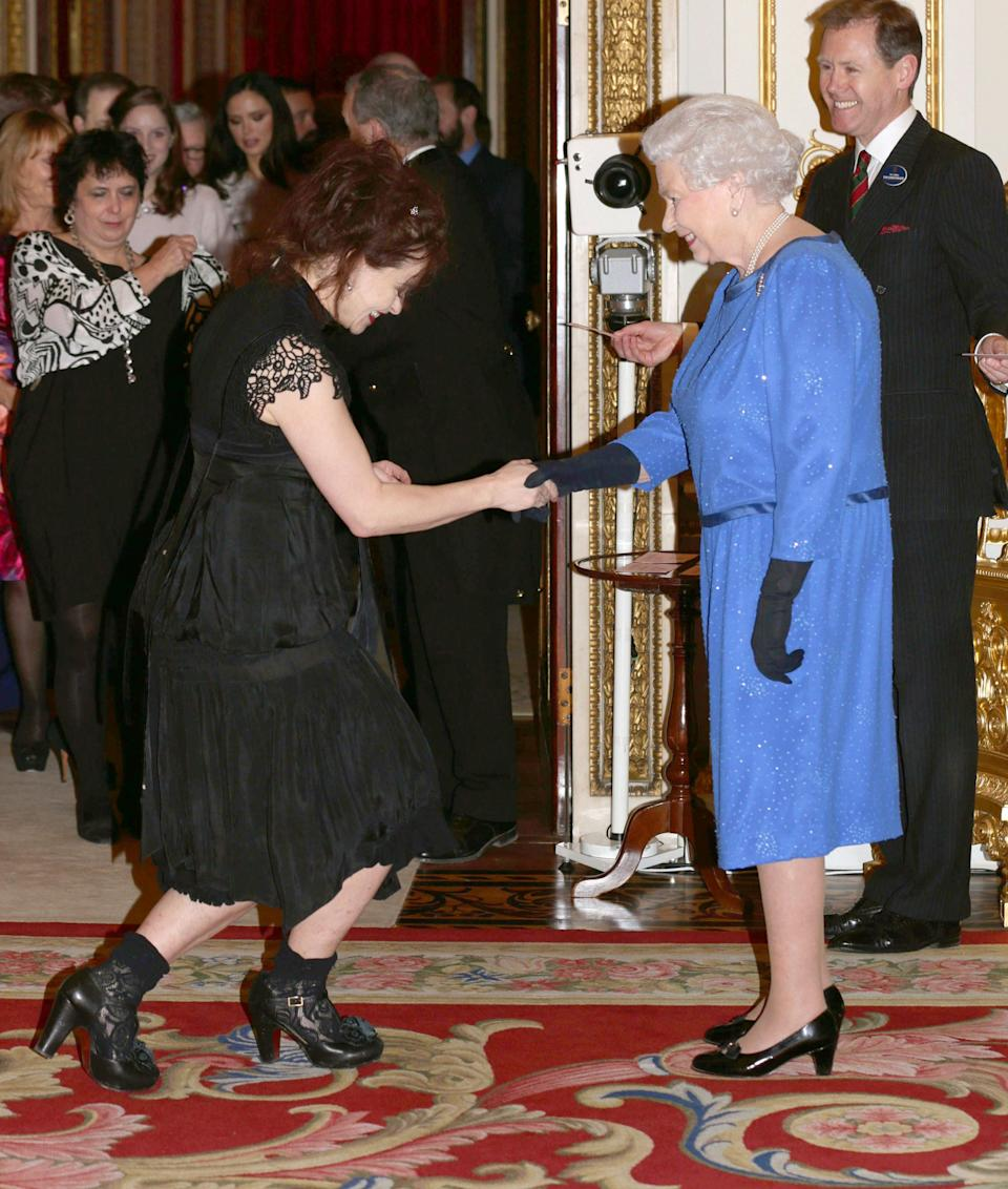 <p>Helena Bonham Carter met the Queen during a Dramatic Arts reception at Buckingham Palace and wasn't going to let the royal greeting get in the way of her personal style. The actress chose a gothic dress complete with a corset and co-ordinating lace shoes for the occasion. <em>[Photo: Getty]</em> </p>