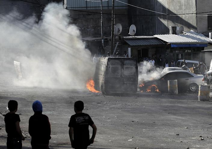 Palestinian youth look at burning cars during clashes with Israeli security forces in east Jerusalem on October 30, 2014 (AFP Photo/Ahmad Gharabli)