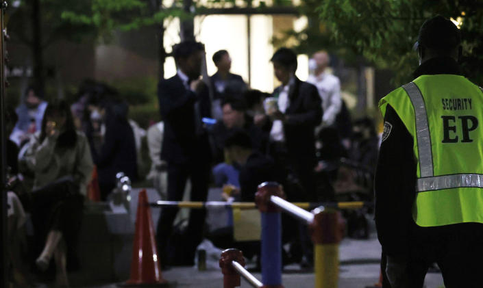 A security person stands guard as people drink at a park in Tokyo on April 21, 2021. Trains packed with commuters returning to work after a weeklong national holiday. Frustrated young people drinking in the streets because bars are closed. Protests planned over a possible visit by the Olympics chief. As the coronavirus spreads in Japan ahead of the Tokyo Olympics starting in 11 weeks, one of the world's least vaccinated nations is showing signs of strain, both societal and political. (Takuto Kaneko/Kyodo News via AP)